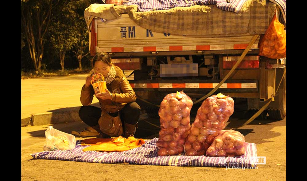 11月17日22:30,仙林某小区外的马路边,一位中年妇女守着她的苹果摊吃泡面。她和丈夫来自山西。苹果2.8元一斤,要比超市便宜不少,但天冷人少,苹果久久没有卖出去。(王剑/摄)