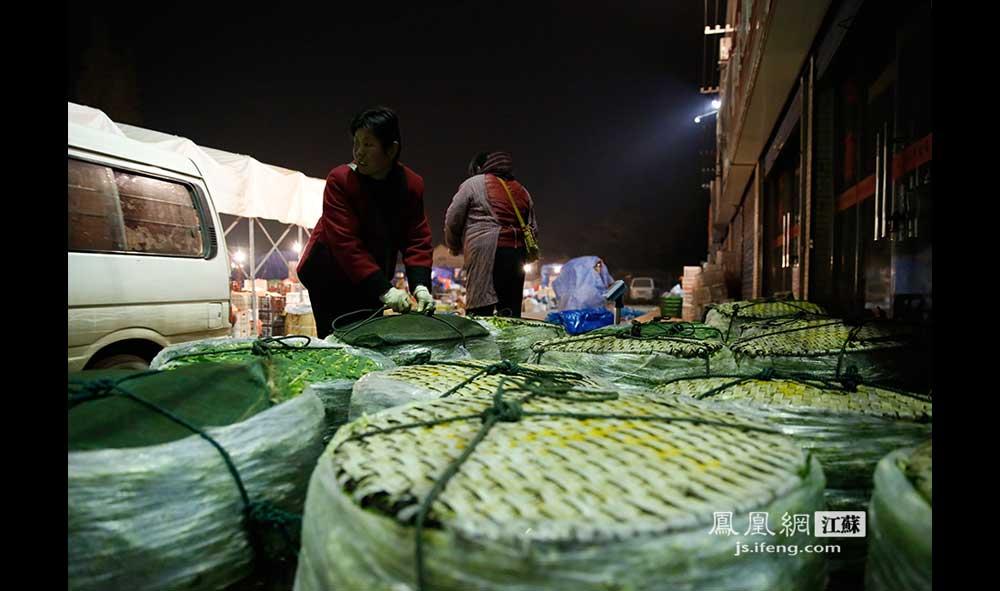 11月19日1:24,栖霞区晓庄农副产品批发市场,一位中年妇女将一筐一筐的蔬菜从车上卸下来。每筐蔬菜重七八十斤。这个市场的菜贩们说,近些年生意不好做,因为周边好多居民因为搬迁离开了,买菜的人少了。每月1500元的摊位费也加重了他们的成本。(王剑/摄)