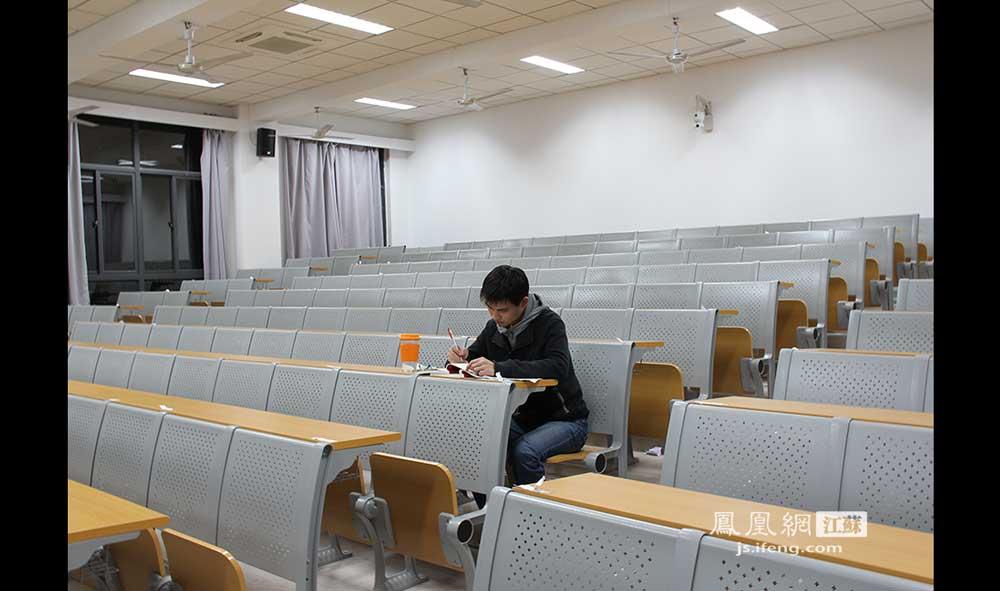 11月17日0:16,南京大学鼓楼校区一自习室内,偌大的教室里只空空荡荡地坐了孙同学一个人。他是南大医学院09级的学生,正准备明年1月份的研究生考试。(王剑/摄)