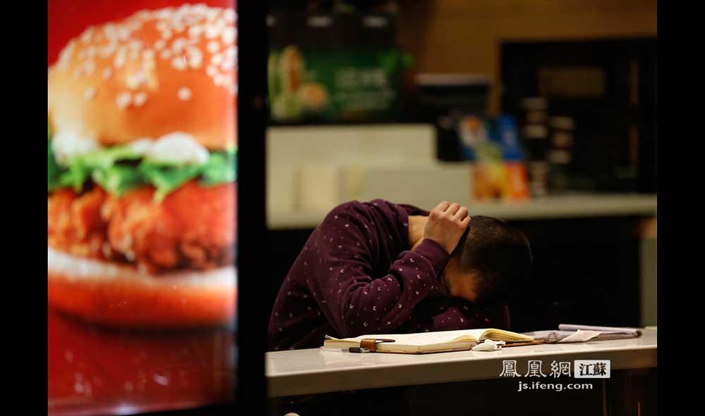 11月17日1:17,南京师范大学鼓楼校区校门外的一家快餐店内,一位男同学趴在桌上睡着了。(王剑/摄)