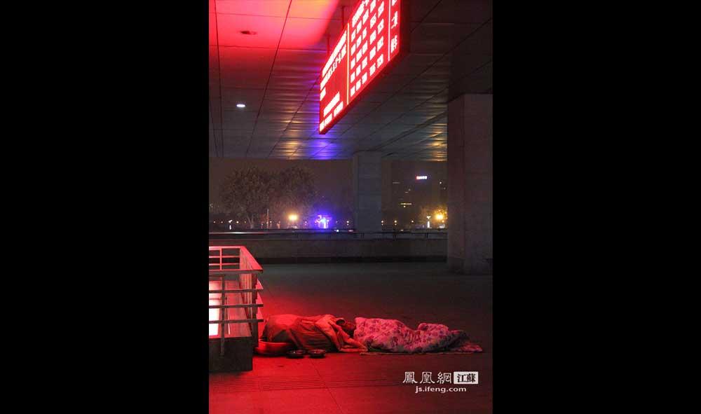 11月16日4:28,南京火车站广场,一名流浪汉在火车信息显示屏下睡觉。他不断说着梦话,发音含糊,声音很大,在清冷的黑夜里没人注意他。(王剑/摄)