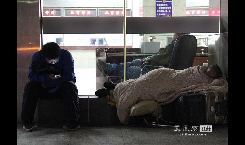 11月16日4:18,南京火车站,一位旅客躺在行李箱上睡觉,边上的小伙子埋头看手机。(王剑/摄)