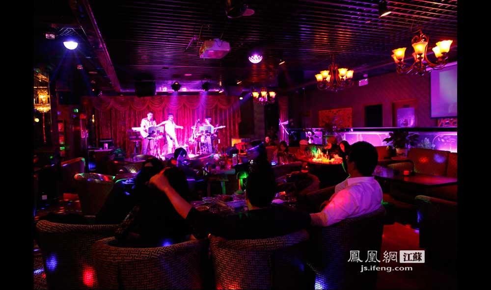11月18日0:30,1912街区内的一家酒吧,几位客人在绚烂的灯光下听乐队演唱。这家酒吧一扎橙汁要价120元,酒吧伙计说这是最低消费。(王剑/摄)