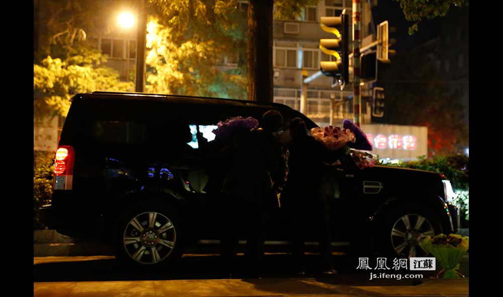 11月17日23:49,南京1912酒吧街,当一辆豪华SUV停在路边后,两位花贩立刻围了上去。1912街区内的花贩以中年妇女居多,每天晚上七八点出门,凌晨三四点回家。每束花50至60元不等,生意好的话,一晚上能卖出两三束。(王剑/摄)