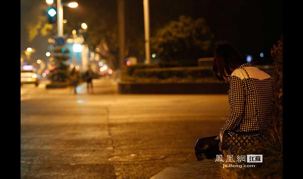 11月16日1:08,新街口,一位年轻的姑娘坐在空旷的街头低着头,久久没有离去。(王剑/摄)