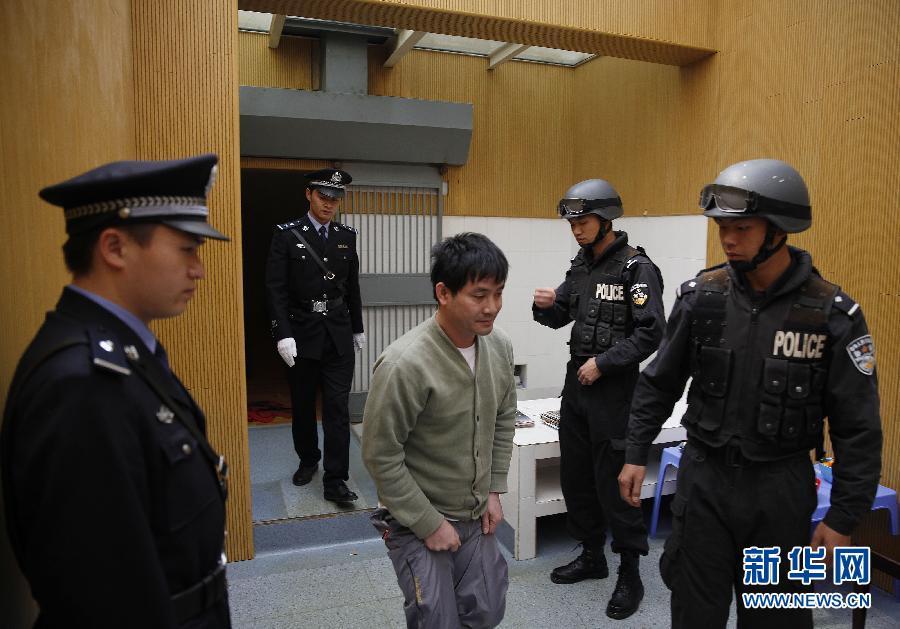 """3月1日,制造震惊中外的湄公河""""10·5""""惨案的4名罪犯糯康、桑康·乍萨、依莱、扎西卡,在云南昆明被押赴刑场执行死刑。新华社记者在羁押糯康的监所中目击了糯康被押赴刑场前的最后40分钟。当日13时20分,糯康坐在床上将裤子穿了起来,在特警的看守下,糯康上了厕所。图为糯康在过渡监室中跑向洗手池。"""