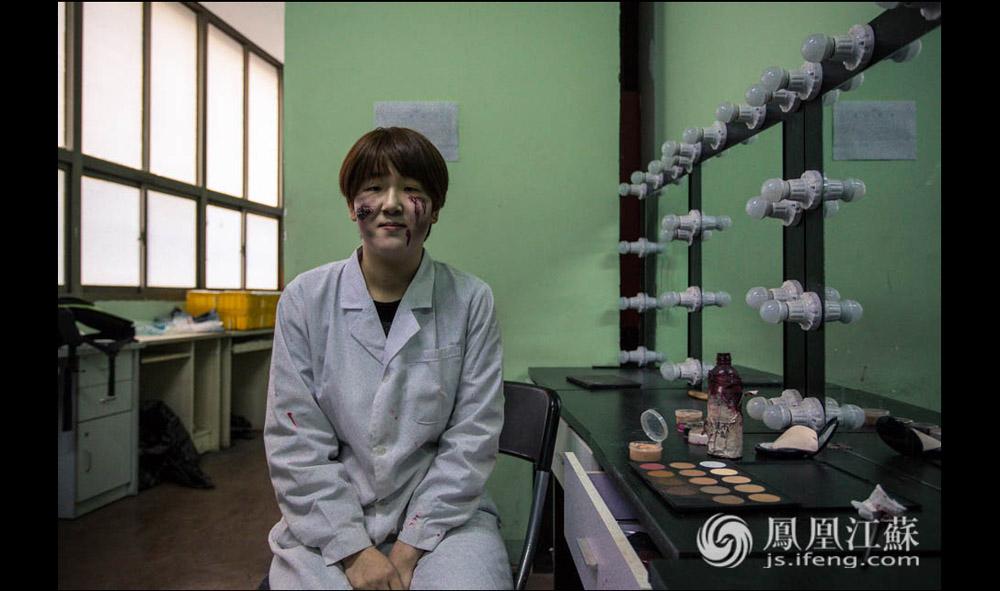 """这里的NPC化妆技术都是经过专门培训的。史亚楠介绍说,他们会先用白粉""""打底"""",让自己的脸呈现出""""惨白惨白""""的效果、接着用眼影画出阴影,勾勒轮廓、最后就是涂上血浆和皮肤油彩。每当遇到特殊的节日,这些""""NPC""""们还要为自己画上""""重妆""""。他们会将棉花贴于脸部再涂上油彩,制造腐烂的效果。每次画""""老人妆""""的时候,这些NPC们还会用特殊的化妆技巧细心地为自己添上皱纹。(胥大伟 陈娟/文 杨光泽/摄)"""