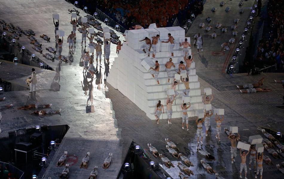 表演者们在将白色的盒子抬入场内,走向场地中央。据说组织者本来要302个盒子,代表奥运会的302个小项,决出302块金牌的含义。