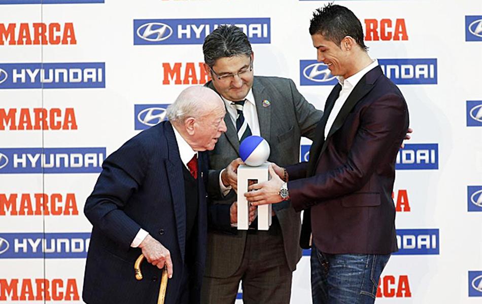 北京时间3月18日晚,西班牙《马卡报》颁发了2011-12赛季西甲各项大奖。C罗获得最佳球员奖,而穆里尼奥则得到了最佳教练奖,梅西领走联赛最佳射手,巴萨门将巴尔德斯成最佳门将,索尔达多成西班牙本土最佳球员。图为迪斯蒂法诺为C罗颁奖。