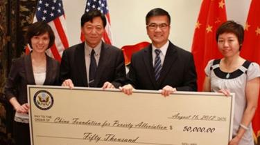 2012年8月16日美国驻华大使馆骆家辉大使向中国扶贫基金会递交捐赠支票