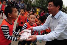 中国儿基会副秘书长乌振英给孩子发放蜜儿餐