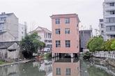 """把房子建在河道上的违建例子可不止一个。2013年3月29日左右,浙江省温州市平阳县鳌江镇一幢建在水上的楼房的照片出现在微博上,引发网友热议,不少网友戏称为""""平阳最牛水上公寓""""。照片显示,楼房底部由八根直径约一米的水泥墩架起,凌空于水面之上,远远看去,粉红色的楼房格外显眼。29日,平阳县水利局办公室工作人员表示,该房子已确认为违法建筑,正准备拆除。(实习编辑李丹)"""