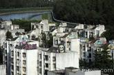 """5月28日,鹿丹村楼顶不少被涂鸦。""""能进鹿丹村非常不容易,大帮人排着队等。""""——陈克仁,鹿丹村业委会主任 从深圳最高楼——京基100大厦上,可以清晰俯瞰鹿丹村的全景图:夹在滨河大道和深圳河之间,与香港仅一河之隔。无论当年还是如今,这里都是深圳的一个黄金位置。1989年竣工的鹿丹村无疑是当时深圳最高档的小区,并曾被评为""""全国第一文明社区""""。 现在的人已经很难想象,这个如今破败不堪的小区,当初曾经多么显赫。鹿丹村在1987年开发建设、两年后全面竣工,是深圳的大型福利住宅小区。"""