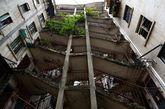 7月9日,广西南宁市,在唐山路一居民区里面有一栋很奇特霸气的楼层建筑。楼层之间通过一个双向楼梯层层相连,连连相扣,十分霸气。这栋建筑的奇特之处在于它是两栋居民建筑连起来的楼层建筑,总共有七层,从中间楼梯上去,两栋楼之间都可以通过同一个楼梯互相通行。站在楼梯底下往上看,让人不得不被这栋楼层建筑的霸气所倾倒,十分震撼。(实习编辑:石君兰)