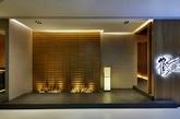"""鹤一烧肉:设计理念抽象的还原了日本大阪鹤桥地区的拥挤的街道建筑形象,餐厅的两个入口安排在""""山墙""""(中国建筑语汇)上,进入餐厅三角型的坡顶映入眼帘,。我们刻意将房檐压低至2.1米,意图用强烈的三角形房顶来表达日式建筑与山林的关系。(实习编辑:陈尚琪)"""