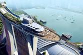 """新加坡 滨海湾金沙   滨海湾金沙酒店是一家耗资50亿美元的综合度假胜地,共有55层,楼顶上还建有一个巨大的泳池。此外还有一条室内运河、一座形似莲花的博物馆、商店、餐馆、剧院、博物馆和赌场。这一设计被一些人描述为由类似顶部设有一个下行甲板的三个板球桩组合而成。""""(实习编辑:周芝)"""