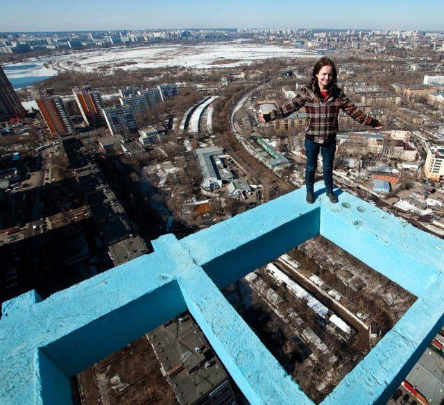 少年不顾危险攀建筑边缘 高空拍摄享受快感