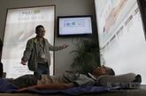 有床垫厂商通过显示屏演示其产品的分散压力效果。