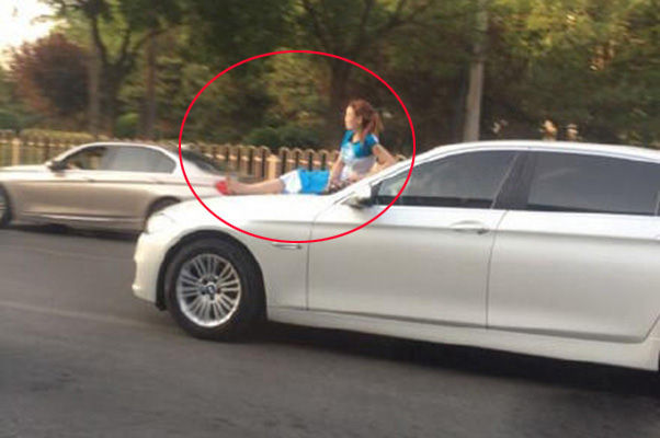 女子坐在行驶中的轿车