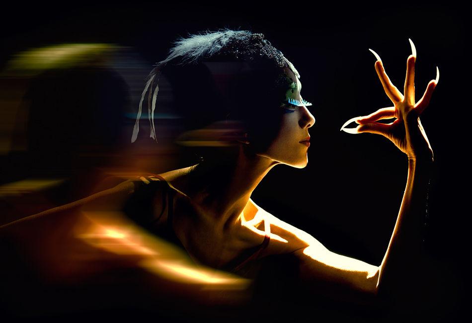 """杨丽萍,1958年生于云南,洱源白族人,自幼酷爱舞蹈。1971年进入西双版纳州歌舞团,九年后调入中央民族歌舞团,并以""""孔雀舞""""闻名。1992年,她成为中国大陆第一位赴台湾表演的舞蹈家。1994年,独舞《雀之灵》荣获中华民族20世纪舞蹈经典作品金奖。2003年,杨丽萍任原生态歌舞《云南映象》总编导及主演。2009年,编导并主演《云南映像》姊妹篇《云南的响声》,再获成功。在2012年央视春晚以舞蹈《雀之恋》,再展舞蹈诗人的风姿。"""