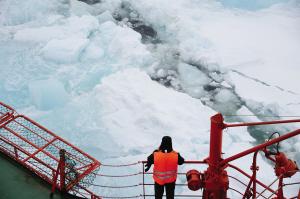 一名游客在船舷上看冰块破裂的壮观场景。