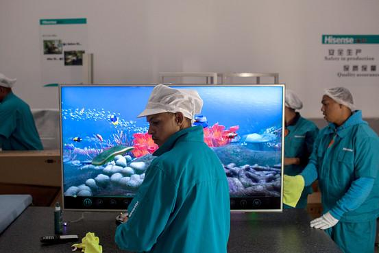 海信支付给南非开普敦电视机工厂工人的工资低于中国工厂水平。 凤凰财经综合 据华尔街日报报道,从海信(Hisense Co.)位于南非开普敦的生产线上每下线一块闪着绿光的电视机主板,就意味着中国朝着新的全球制造业基地又迈出了一小步。 这条生产线的八名非洲技术员通过电脑监控组装流程,他们也有加快工作速度的动力。经过不到一年的操作,他们生产主板的速度已能和中国技术员媲美,生产每块主板仅需70秒。 但不足之处是,同样生产这些产品,海信中国工厂的员工人数要比南非少一半。在南非,每位技术员负责监控一台机器,而中国工