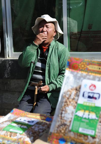 敬老院老人開心地品嘗拉薩卓依瑪綠色食品有限公司的產品爆青稞。