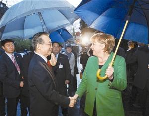 22日晚,温家宝在德国出席默克尔举行的晚宴,默克尔在雨中迎候。