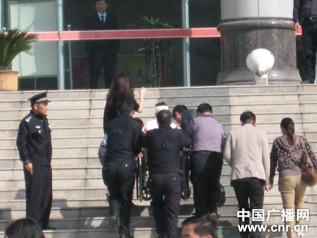周岩被抬进法庭(图片来自中国广播网)
