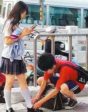 台南二中高一男生在路上帮女友绑鞋带镜头,引起网友热烈议论.图片