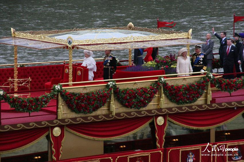 英国女王伊丽莎白二世(穿纯白色礼服者)在巡游庆典船上向民众招手。