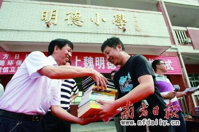 南方日报(左)给明德小学(右为小学校长)赠书.