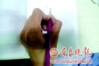 一市民在用左手写字。本报记者 李大鹏 摄
