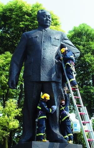 消防员清洗陈毅市长雕像迎国庆