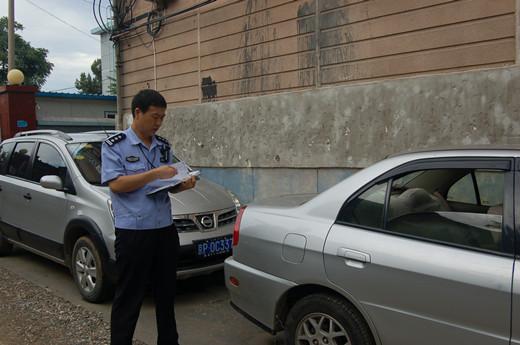 在社区巡逻时发现一辆未关车窗的汽车,记下车号联系车主高清图片