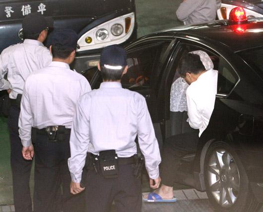 """前台当局""""行政院秘书长""""林益世(右)昨天遭台特侦组依贪污罪起诉,并在警方的戒护下移审台北地院开接押庭,林益世下车时刻意避开媒体镜头,以螃蟹横行的方式进入地院开庭。 图片来源:台湾联合新闻网"""
