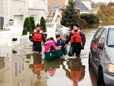 警方划船营救被困居民。(美国《星岛日报》)