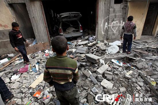 当地时间2012年11月19日,在加沙城东部,巴勒斯坦人查看遭以色列空袭的房子。