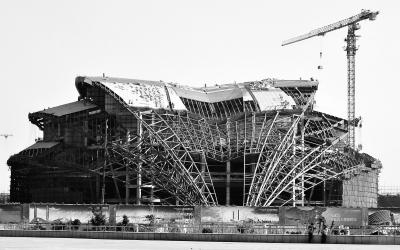 国博会议中心钢结构主体已安装到位,并开始安装外部玻璃幕墙.