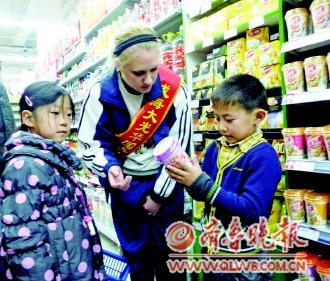 图为小学生在购物过程中与外教中止英语交流。 记者 刘洁 摄