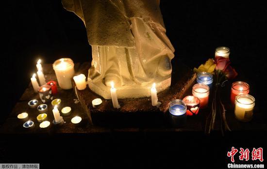 图为14日晚,当地民众为校园枪击案遇难者举行烛光默哀。