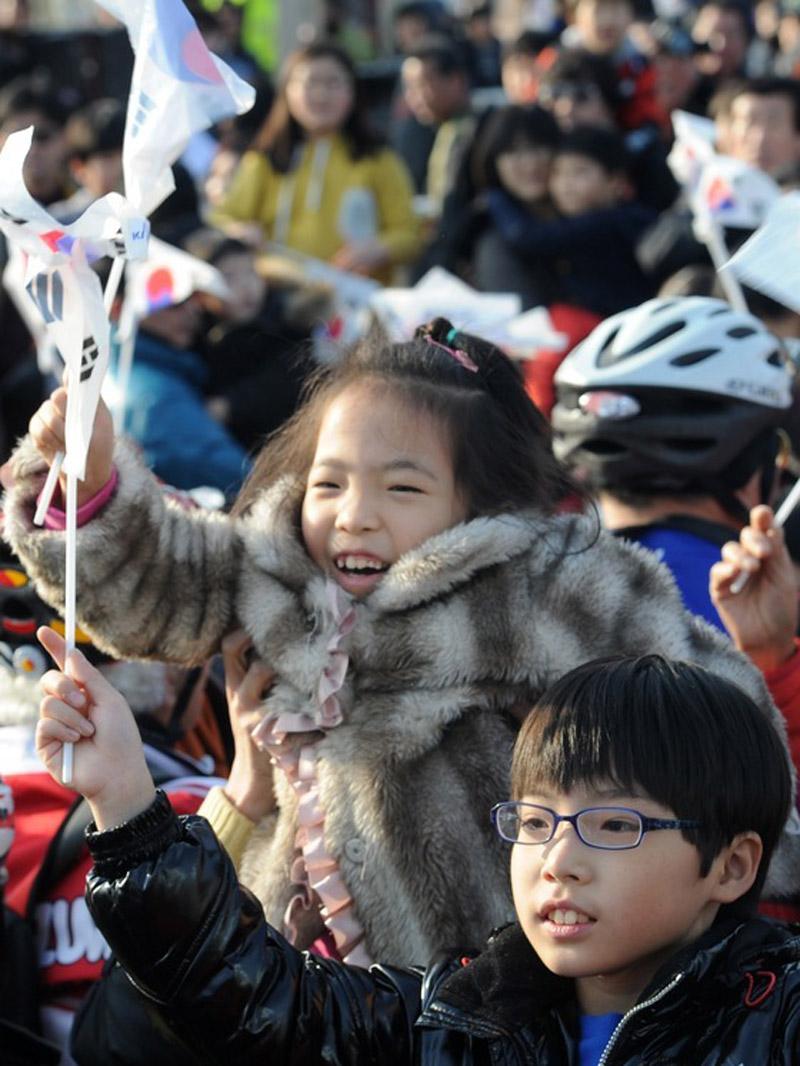"""30日,韩国小朋友摇旗庆祝""""罗老""""号发射升空。"""