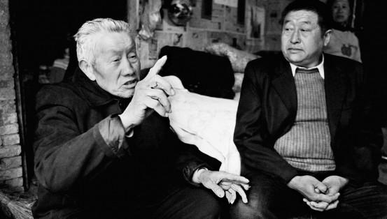 住在当年知青宿舍对面的村民许同礼(左)回忆李克强的知青生活。