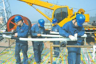作人员用卷扬机牵引电缆线头.-电缆入地 广安拆除电力铁塔