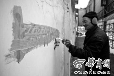 """1月31日,博思特家政的朱师傅,沿着渭南市朝阳大街清理路边的""""野广告"""" 本报记者 赵雷 摄"""