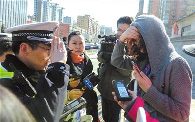 4月11日,一名闯红灯的女子接受交警教育。  (资料图片)京华时报记者蒲东峰摄