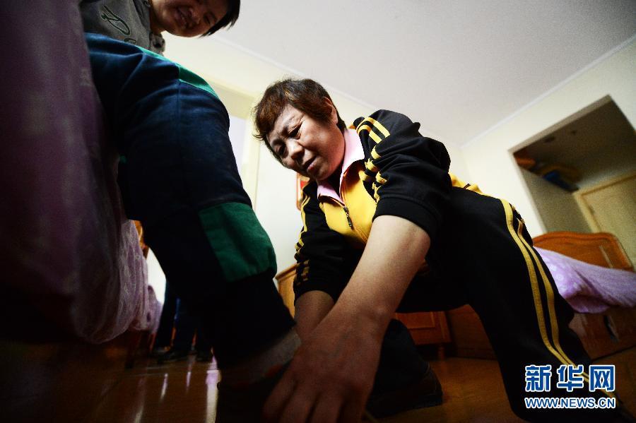 5月15日,王桂英在为一名智障孩子穿鞋系鞋带. 新华社记者王凯摄图片
