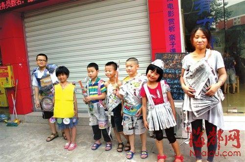 """孩子们穿上用报纸制作的衣服 n栏目主持 廖庆升 """"你穿这个裙子太好玩"""