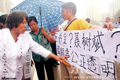7月10日王书金受审,有市民在法院外举牌要求公开聂树斌案案情。