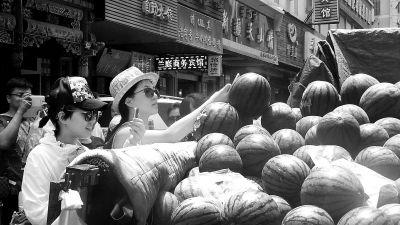 在售卖的西瓜上雕刻出各种各样形态逼真的脸谱,荷花等图案,引来不少